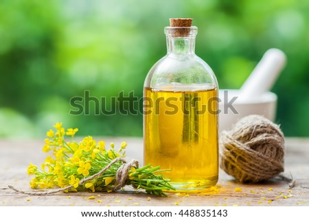 Bottle of rapeseed oil (canola) and rape flowers on table outdoors