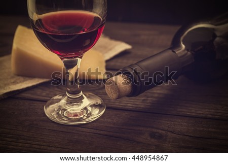 Bottle of red wine with a glass and a piece of parmesan on an old wooden table. Angle view, image vignetting and the yellow toning