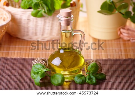 Bottle with grape seed oil with decoration of fresh basil