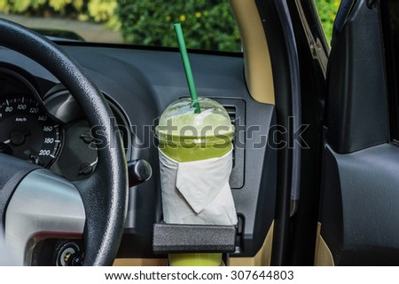 Bottle with the green tea in a car interior
