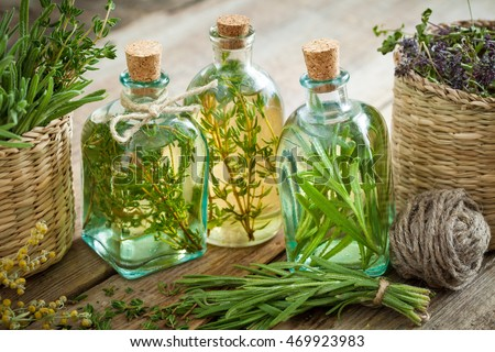 Bottles of thyme and rosemary essential oil or infusion, herbal medicine.