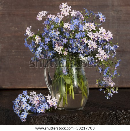 bouquet of flowers in a small blue pitcher glass