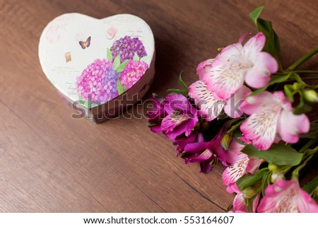 Bouquet of flowers with gift box on a wooden table background