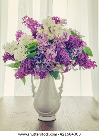 Bouquet of lilacs in a vase on the window.
