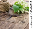 Bouquet of spring flowers lilys of the valley with old rusty antique scissors and ball of brown twine - stock photo