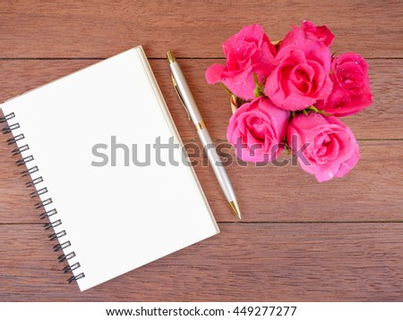 Bouquet pink rose flower in basket, blank notebook and pen on dark wood background with top view