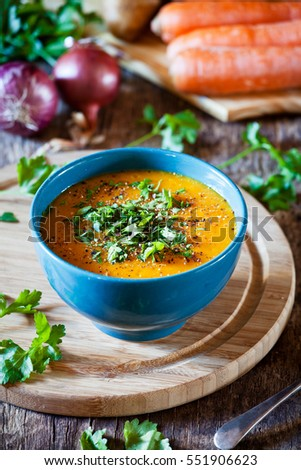Bowl of homemade carrot potato and onion soup with herbs