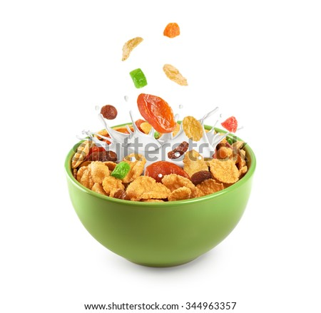 Bowl of muesli and dried fruit isolated on a white background. Splashing milk.