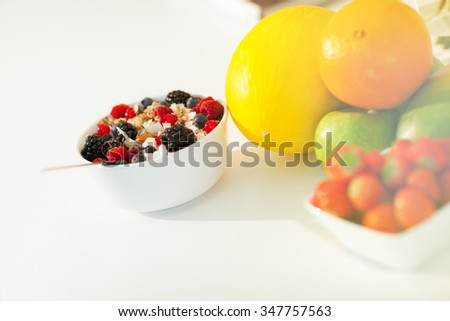 Bowl of muesli with spoon on white sunny table arranged with fresh fruits. Healthy breakfast concept.