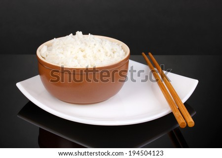 Bowl of rice and chopsticks on plate on grey background