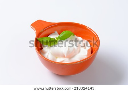 bowl of sour cream with basil on white background