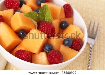 Bowl of summer fruit salad with raspberries, melon, blueberries and mint leaves in white bowl