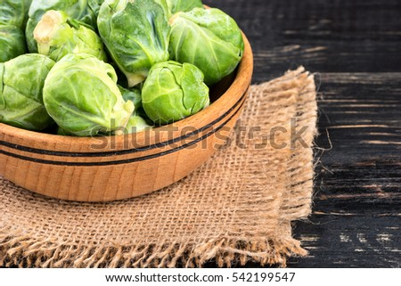Bowl with raw brussels sprouts on sackcloth and table closeup