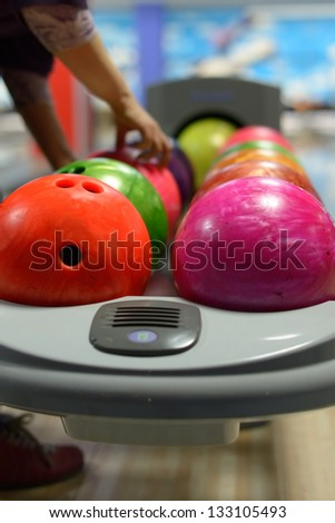 Bowling ball machine with person taking ball in the background