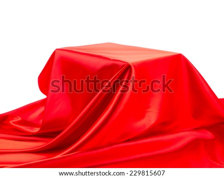 Box in red silk fabric. Located on a white background.