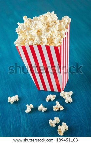 Box of popcorn on blue background