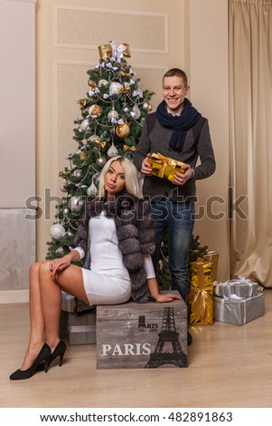 Boy and girl in the New Year.Beautiful girl in the dress and shoes sits on the box and posing, and guy standing at the Christmas tree with the gift in his hands.