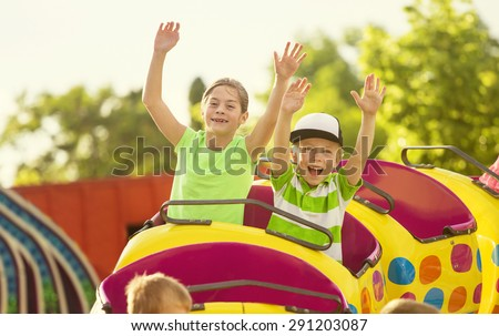 Boy and Girl on a thrilling roller coaster ride at an amusement park with arms raised and yelling with excitement