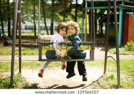 boy and girl on the swings on playground