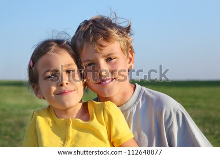 Boy and girl smile together at background of green field and blue sky.