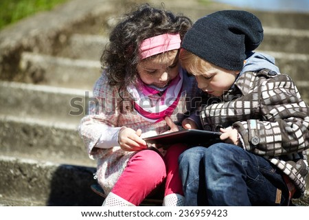 boy and girl using tablet together