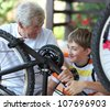 Boy and grandfather fixing bike - stock photo