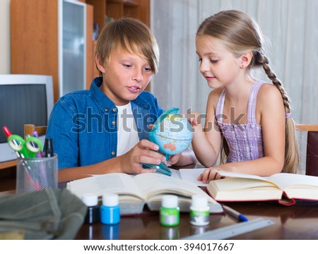 boy and younger sister studying with books indoors