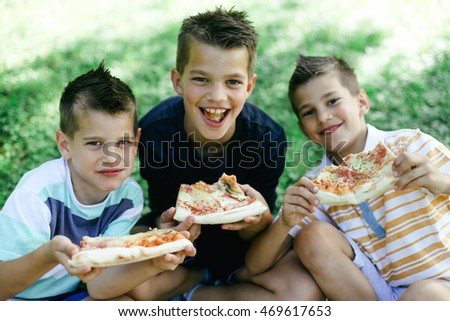 Boy eating pizza having fun in the park.