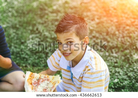 Boy eating pizza in park and having fun.