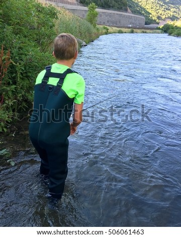 Boy fly fishing on a river next to a road - a canyon in the evening