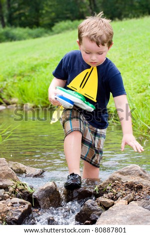 Boy has fun by playing with toy boats in creek at park during spring or summer.