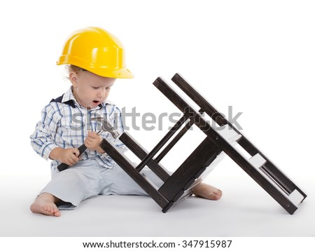boy in protective helmet repairs wooden chair