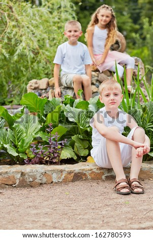 Boy in white shorts and sleeveless t-shirt sits on curb of walkway in park, his friends sit behind him on rocks not in focus