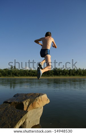 Boy jumps in small river from a stone