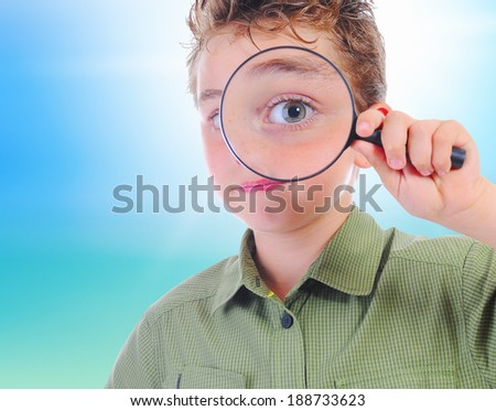 boy looking through a magnifying glass isolated on a white background