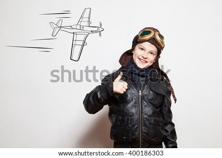 Boy pilot with drawn plane against the with. Pilot with helmet. Pilot with glasses. Pilot giving thumb up.