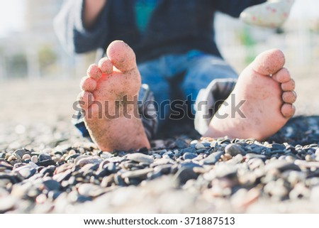 Boy's legs close up sitting on the beach