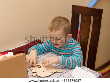 boy sitting at a table with a cardboard box in which lies a wooden constructor
