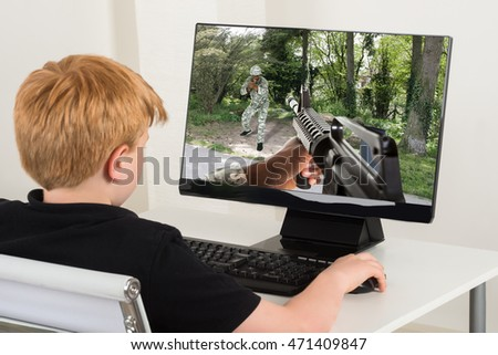 Boy Sitting On Chair Playing Action Game On Computer