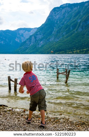 boy throwing rocks into the mountain lake, bohinj, slovenia