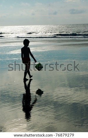 Boy walking on beach.