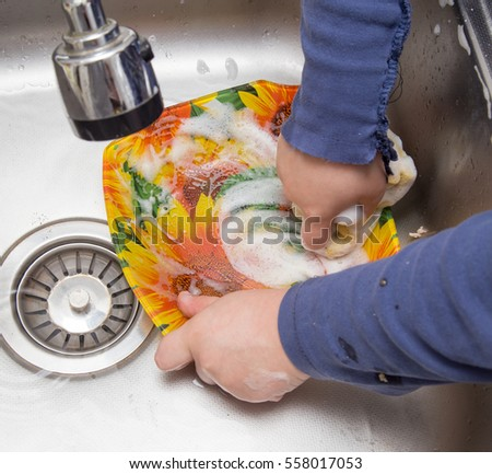 boy washing dishes in the kitchen