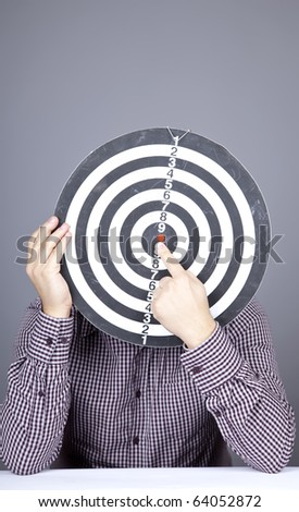 Boy with dartboard in place of head. Studio shot.