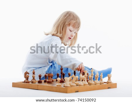 boy with long blond hair playing with chess pieces - isolated on white