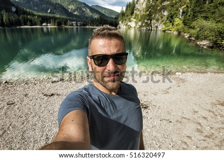 boy with sunglasses that you take a selfie in front of a mountain lake