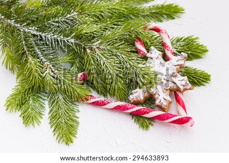 Branch of Christmas tree decorated with heart-shaped candy and gingerbread, selective focus, top view