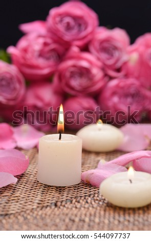 Branch pink rose and petals with candle on mat