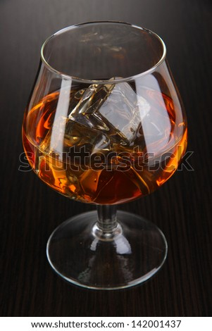 Brandy glass with ice on wooden background