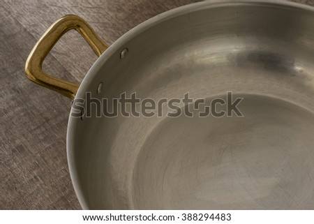 Brass handle and interior of a cooking pot placed on a wooden surface shot at high angle.