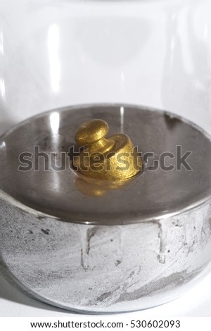Brass weight floats in a beaker of mercury.